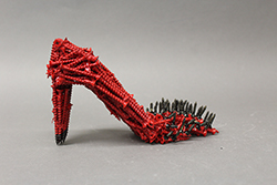 high heel shoe made of red and black nails